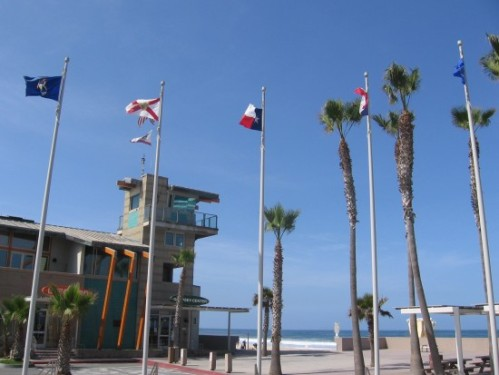 Lifeguard tower behind palm trees and flags.