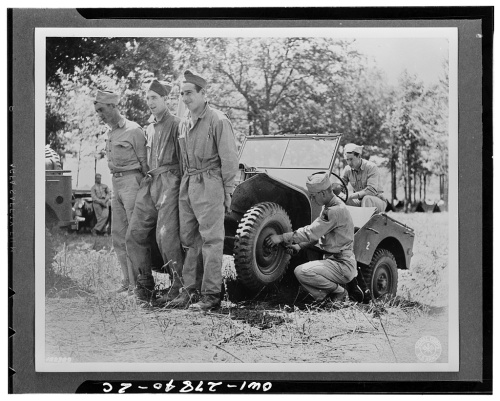 soldiers holding up jeep