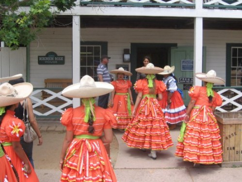 Ladies in Mexican folk costume gather in front of Old Town's Robinson-Rose House.